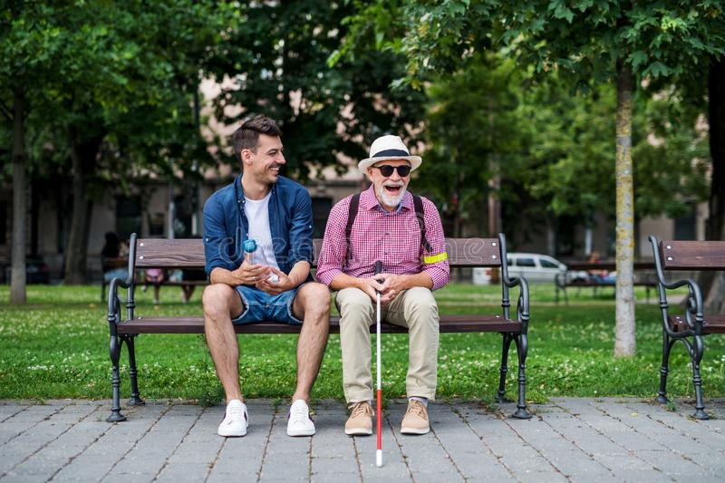 Young man and blind senior with white cane sitting on bench in park in city. stock image