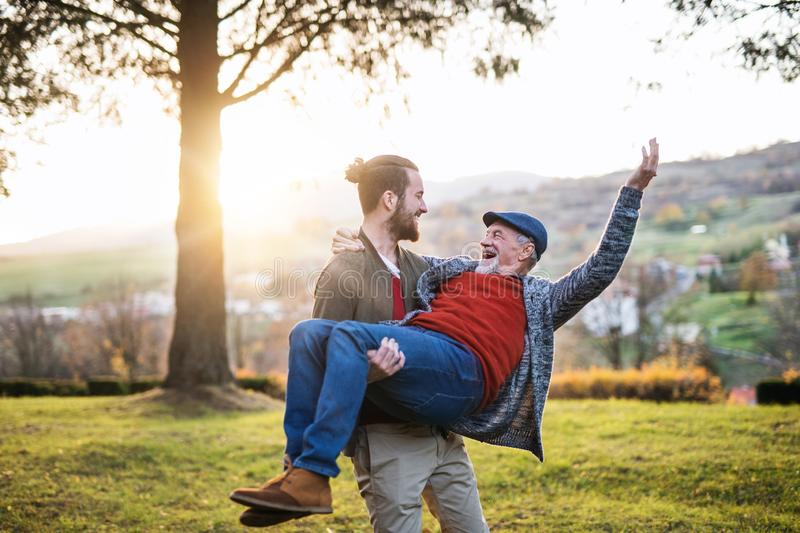 Young man carrying his senior father in arms in nature, having fun. royalty free stock photography