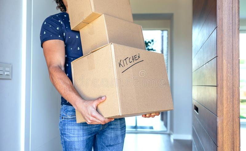 Man carrying moving boxes. Young men carrying moving cardboard boxes royalty free stock photo