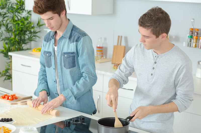 Young men cooking in kitchen stock photo
