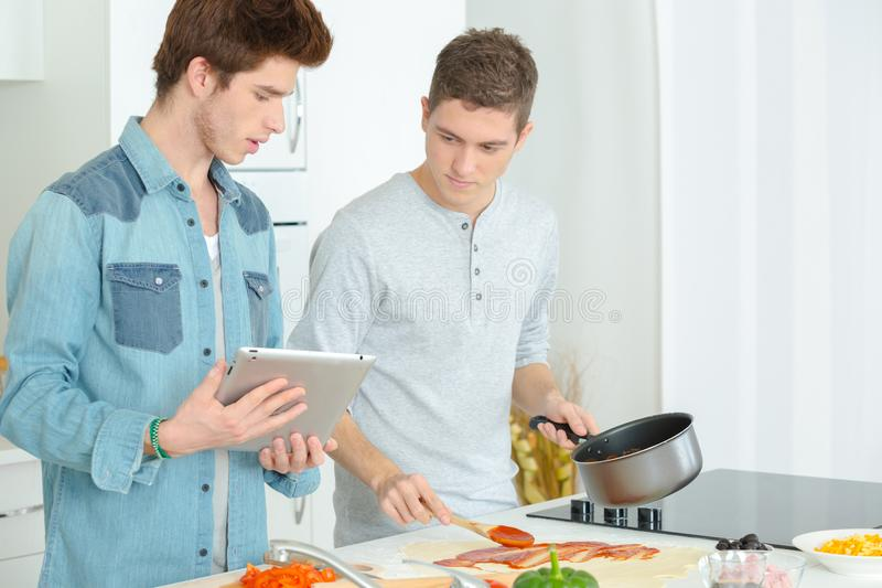 2 young men cooking together at home. 2 royalty free stock photography
