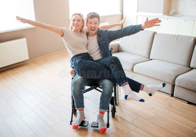 Young man with disability and inclusiveness holding girlfirend on knees. They smile and pose on camera. Cheerful happy royalty free stock photo