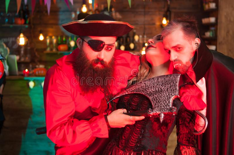 Young men dressed up for halloween party like dracula and a scary pirate killing the witch royalty free stock photos