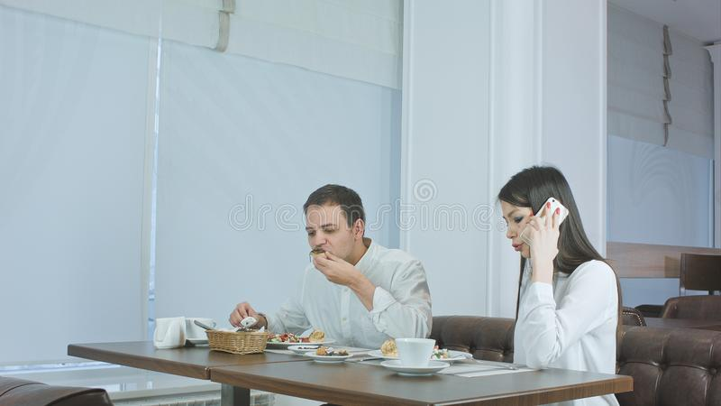 Young man eating while his girlfriend talking on the phone at restaurant royalty free stock photography