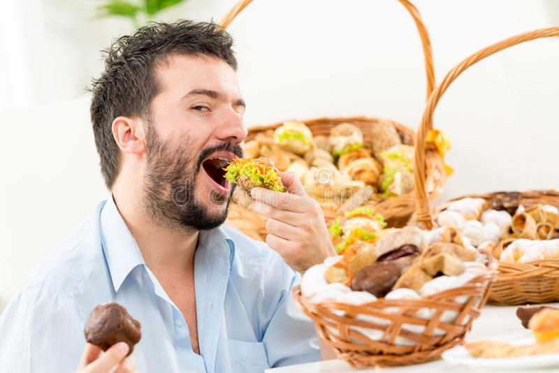 Young Men Eating Pastries. Young bearded man eating a small sandwich,with an expression of enjoyment on his face looking at the camera. In the background you can royalty free stock photography