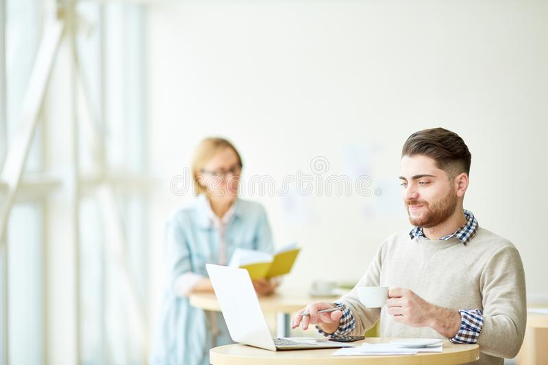Relaxing people with coffee in cafeteria. Young men enjoying cup of coffee and using laptop sitting in cafeteria with women on background stock image