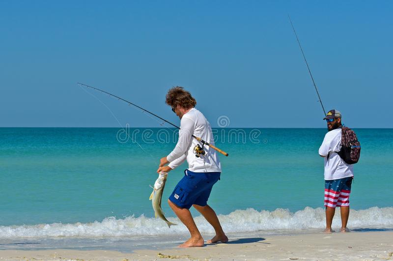 Local Young Men Fishing from Beach royalty free stock images