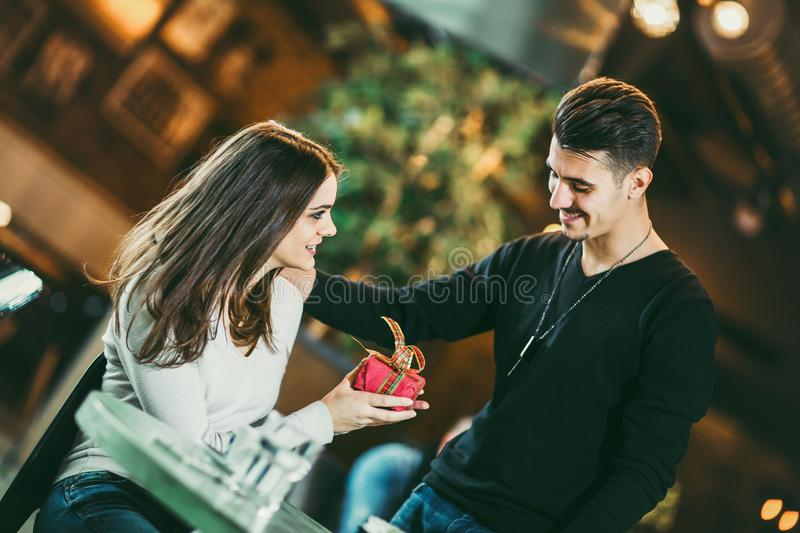 Man gives a gift to a young girl in the cafe royalty free stock image