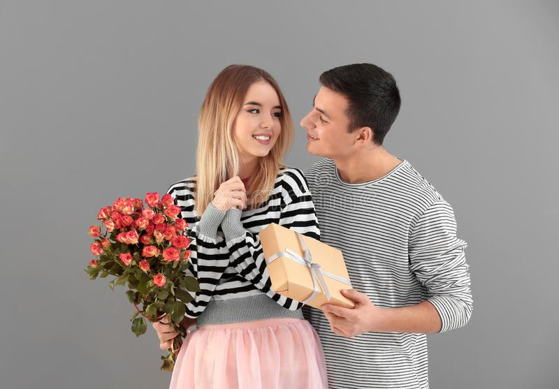 Young man giving present and flowers to his beloved girlfriend on grey background stock image