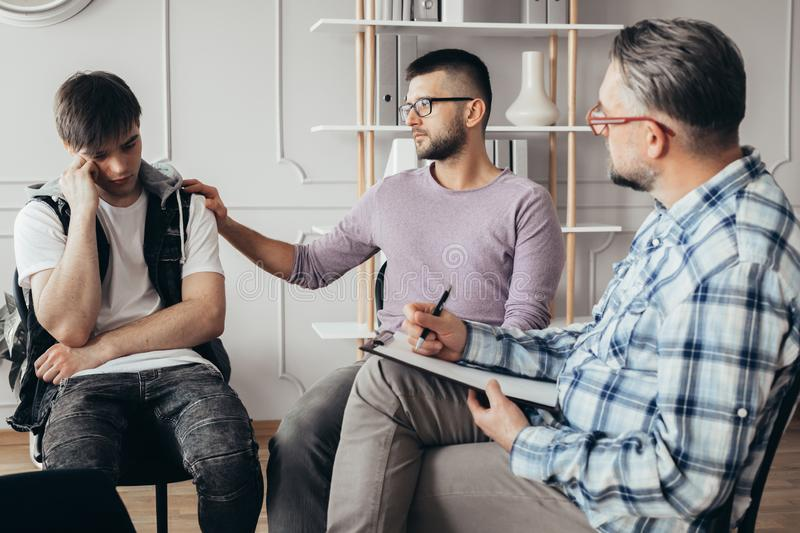 Young man in glasses comforting his friend during meeting with counselor. Young men in glasses comforting his depressed friend during meeting with counselor royalty free stock images