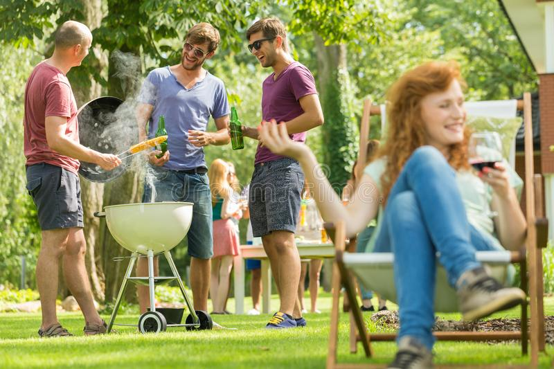 Young men grilling royalty free stock photography