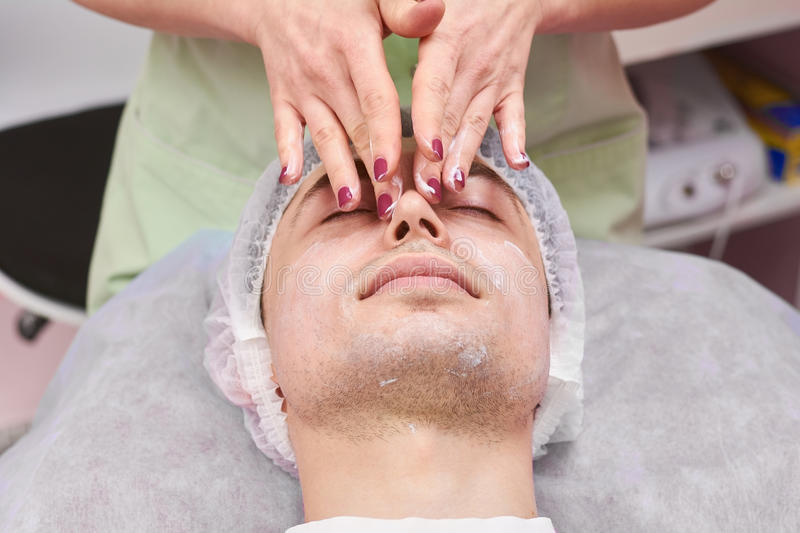 Young man having face massage. royalty free stock image