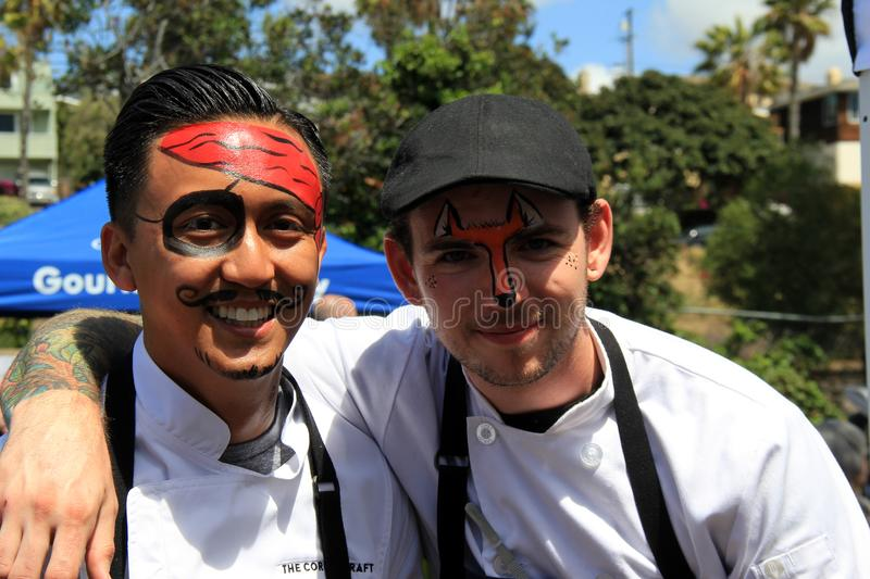 Young men having fun getting their faces painted at food festival, San Diego, California, 2016. Two young men having fun and smiling as they show off their stock photo
