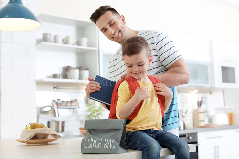 Young man helping his little child get ready for school royalty free stock photos
