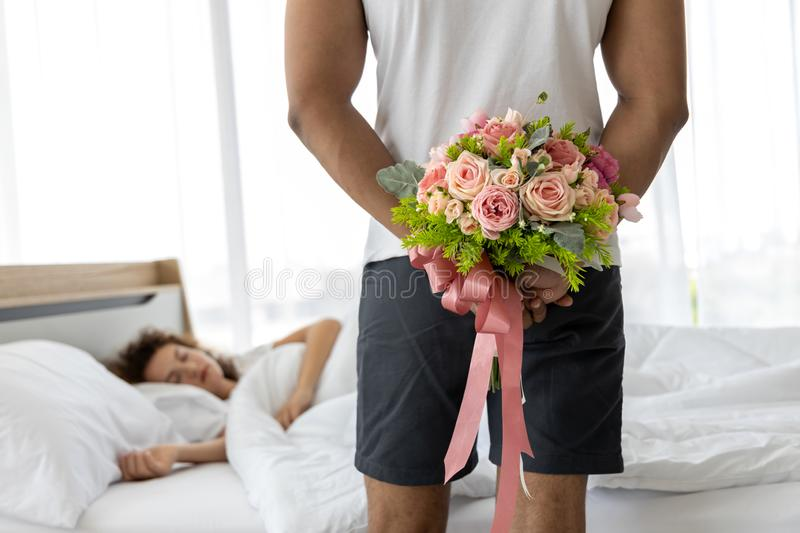 Young man hiding bouquet of flower behind his back before surprise his wife. Beautiful romantic couple in bed room stock photography