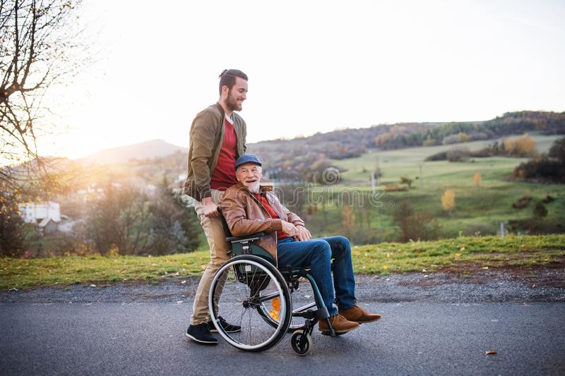 Young man and his senior father in wheelchair on a walk in town. A young men and his senior father in wheelchair on a walk in town at sunset royalty free stock photography