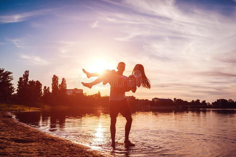 Young man holding his girlfriend in his hands. Couple having fun on summer river bank at sunset. Guys relaxing stock images