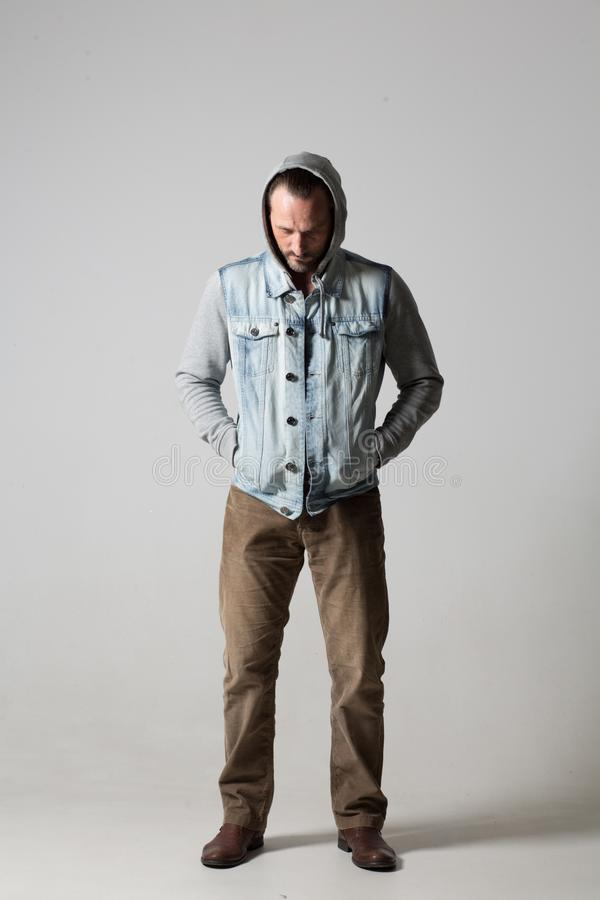 Good-looking unsmiling well-built young man. Young men in hoodie and sleeveless jeans jacket standing on white background stock photos