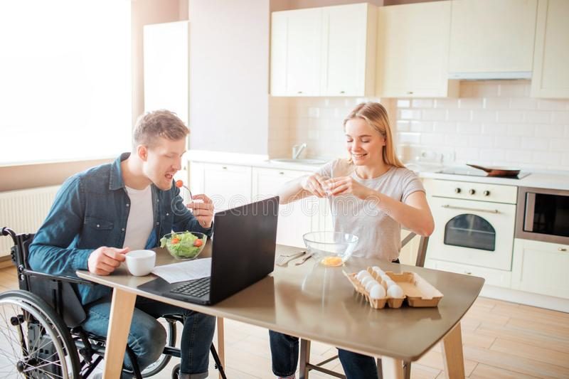 Young man with inclusiveness and special needs eating salad in kitchen. Sit on wheelchair and studying. Young woman sit royalty free stock image