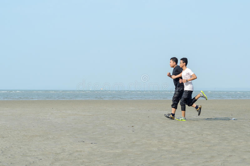 Young men jogging on the beach royalty free stock photography