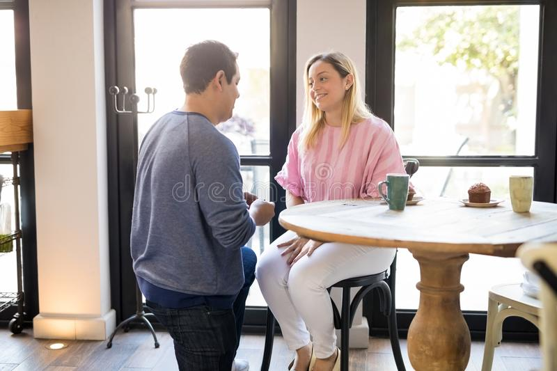 Young man proposing to his girlfriend at restaurant. Young men kneeling in front of his girlfriend and about to make a marriage proposal at restaurant stock photography