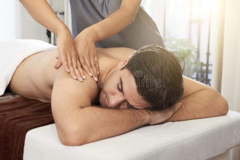 Man getting a massage. Young men lying with his eyes closed and masseuse doing massage on his back in spa salon stock photos