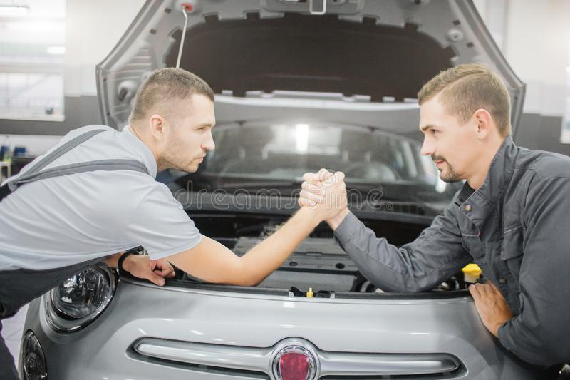 Young men making a deal between each other. They lean to car and hold each other`s hands. Front part of car body is stock photography