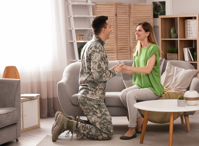 Young man in military uniform with his wife stock photo