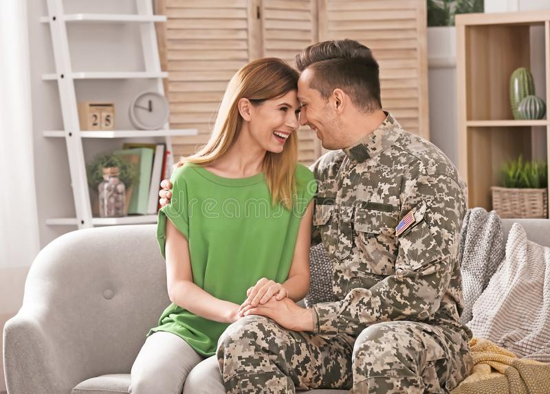 Young man in military uniform with his wife on sofa stock images