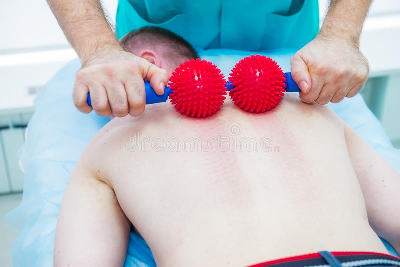 Young man at the physiotherapy receiving ball massage from therapist. A chiropractor treats patient`s thoracic spine in medical royalty free stock photography