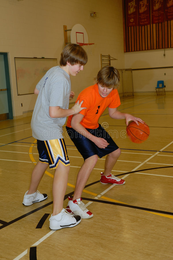 Young Men Playing Basketball. Two young men play basketball in Gymnasium stock photography
