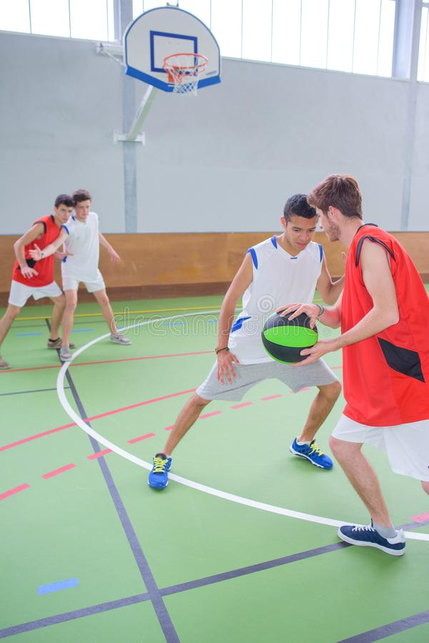 Young men playing basketball royalty free stock images
