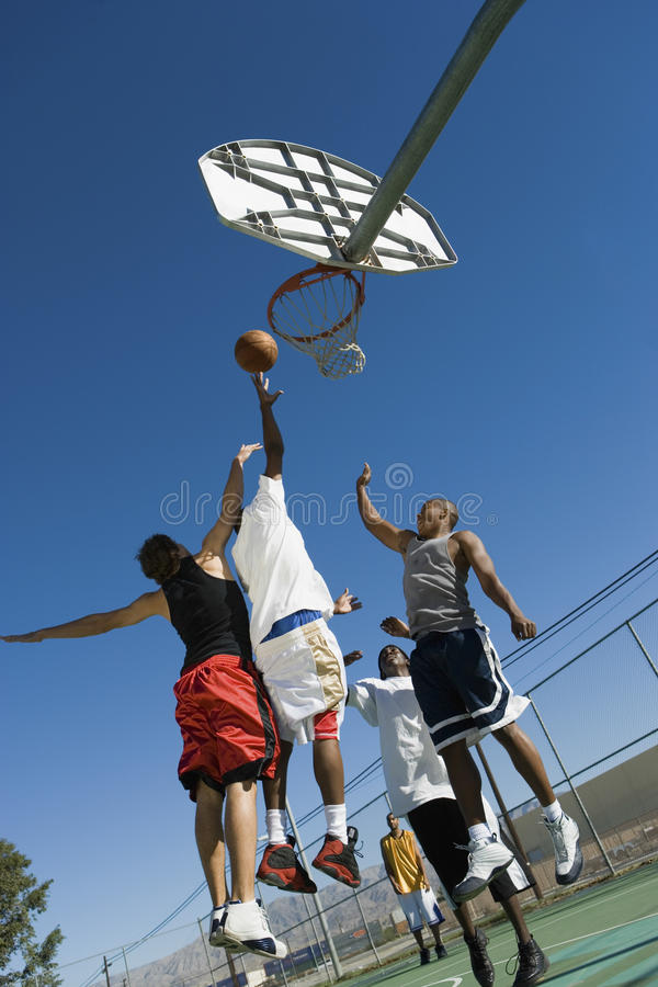 Young Men Playing Basketball On Court. Low angle view of young men playing basketball on court stock images