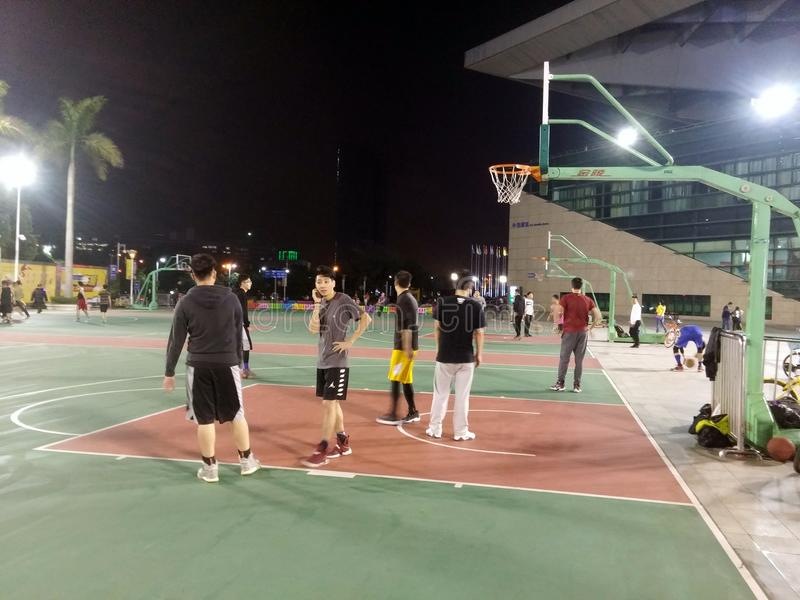 Young men are playing basketball, at night. In Shenzhen, China royalty free stock images