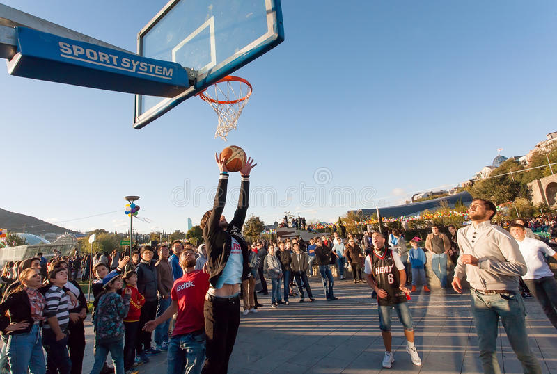 Young men playing basketball outdoor during popular city festival Tbilisoba. TBILISI, GEORGIA - OCT 16: Young men playing basketball outdoor during popular city royalty free stock photo