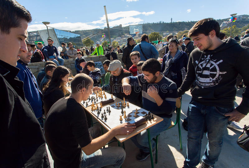 Young men playing chess in crowd of players of competition at city festival Tbilisoba stock photography