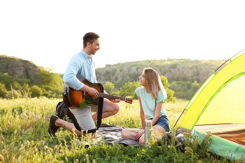 Young man with his girlfriend near camping tent in wilderness stock photography