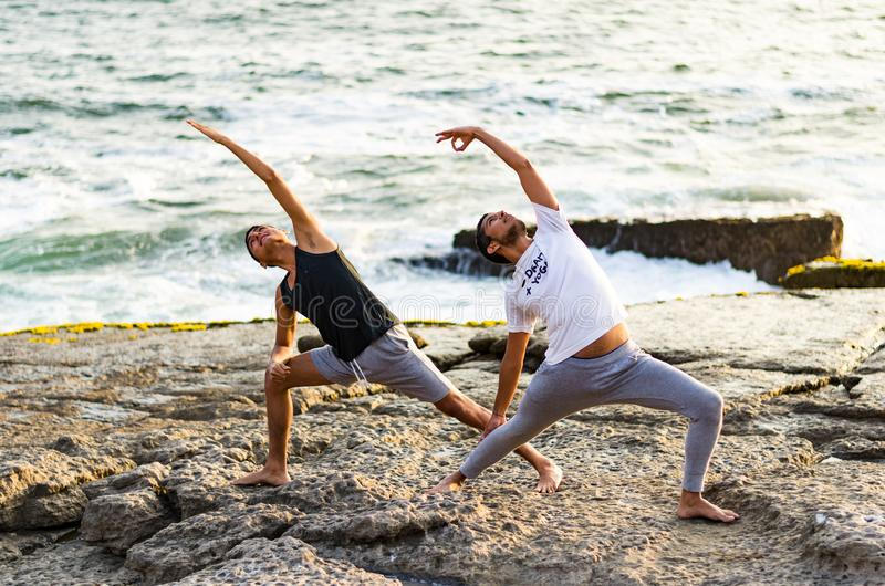 Young men practice balance asanas on Summer yoga session on a beautiful golden beach of Lima - Peru. On a yoga tour, Fulhadhoo, Extended Side Angle Pose Utthita stock image