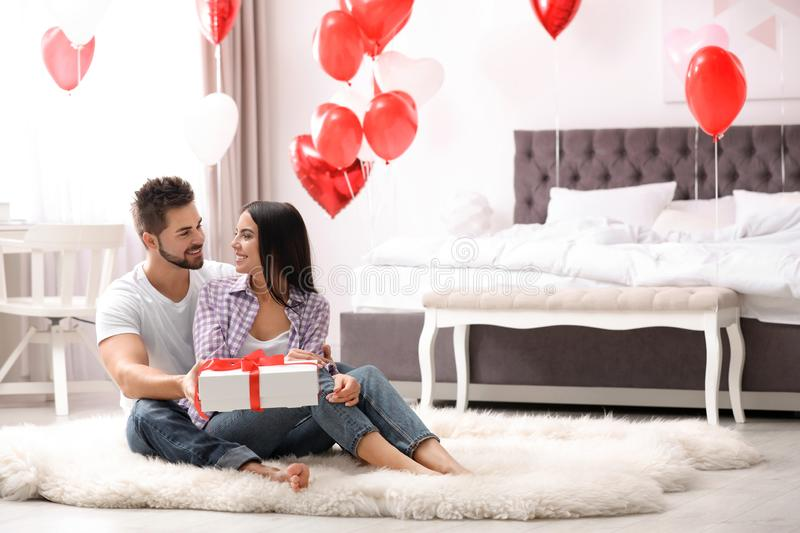 Young man presenting gift to his girlfriend in bedroom decorated with heart balloons. Valentine`s day celebration. Young men presenting gift to his girlfriend in stock photography