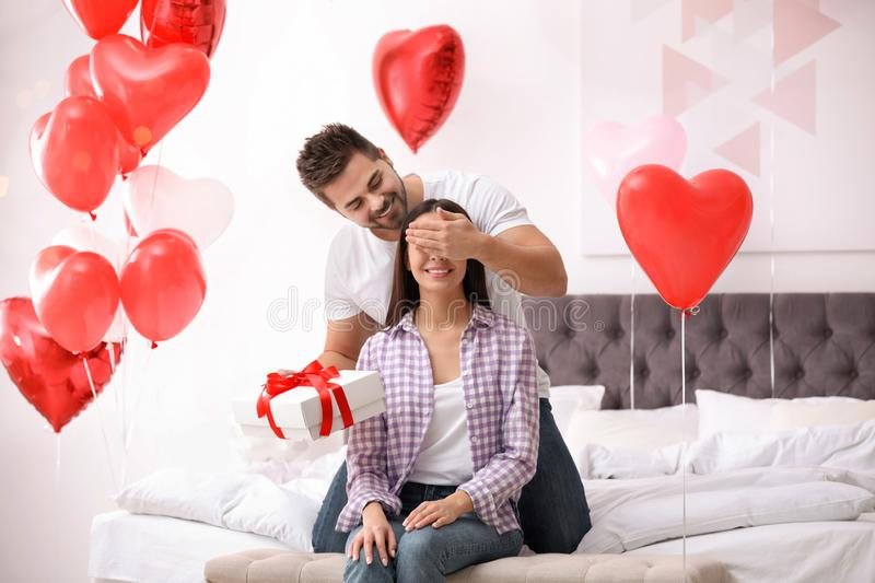 Young man presenting gift to his girlfriend in bedroom decorated with heart balloons. Valentine`s day celebration. Young men presenting gift to his girlfriend in stock images