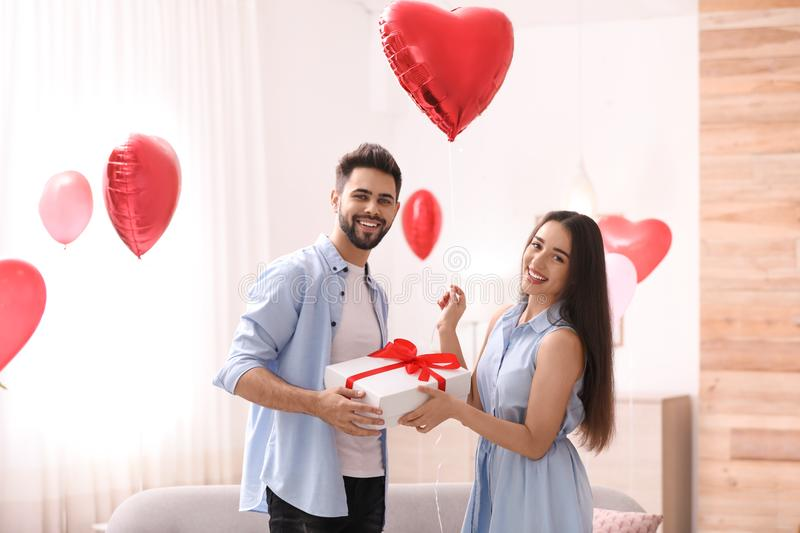 Young man presenting gift to his girlfriend in room decorated with heart shaped balloons. Valentine`s day celebration royalty free stock photos