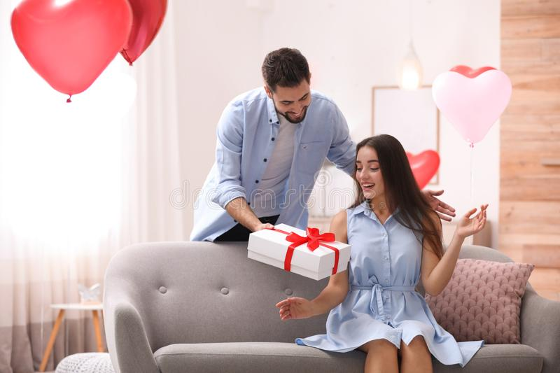 Young man presenting gift to his girlfriend in room decorated with heart shaped balloons. Valentine`s day celebration. Young men presenting gift to his stock photography
