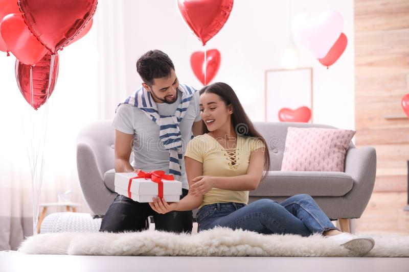 Young man presenting gift to his girlfriend in room decorated with heart shaped balloons. Valentine`s day celebration. Young men presenting gift to his royalty free stock image