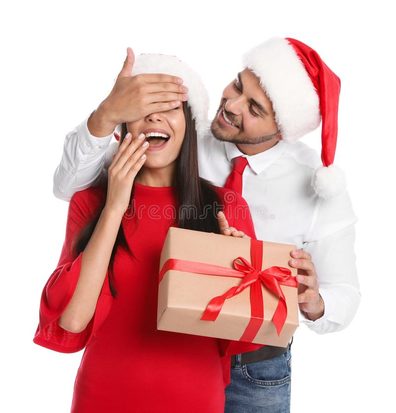Young man presenting gift to his girlfriend on background. Christmas celebration royalty free stock images