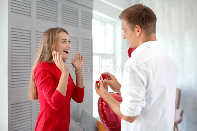 Young man proposing to his beloved with beautiful engagement ring at home. Young men proposing to his beloved with beautiful engagement ring at home stock image