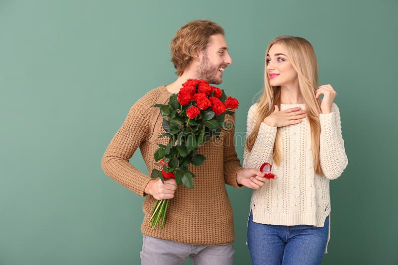 Young man proposing to his beloved on color background. Young men proposing to his beloved on color background stock image