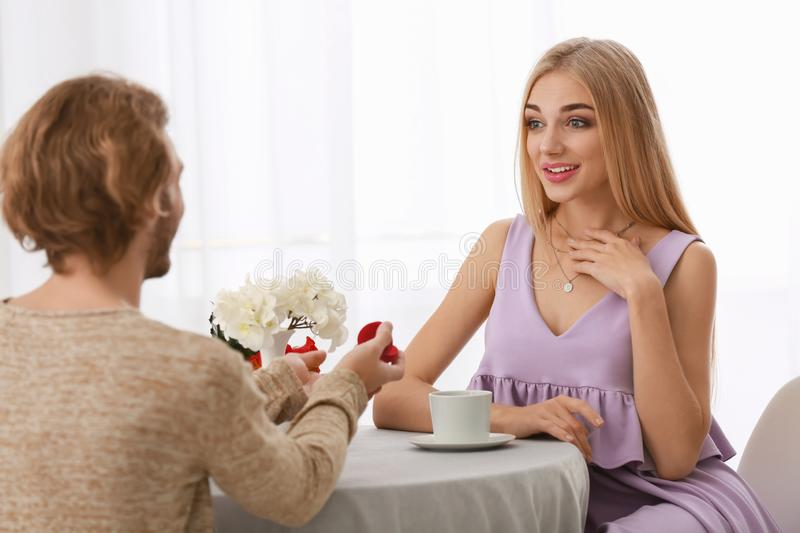 Young man proposing to his beloved on romantic date. Young men proposing to his beloved on romantic date royalty free stock photo