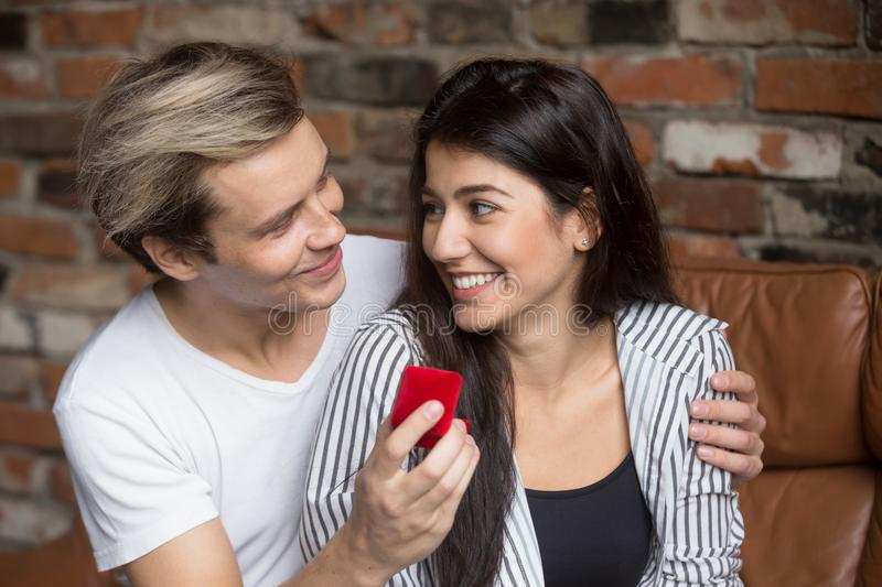 Man proposing to excited woman at home, holding ring box. Young men proposing to women at home on sofa, boyfriend making marriage proposal, asking girlfriend royalty free stock photo