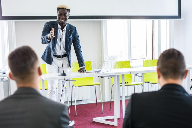 Young man raising hand to ask question. Boss leader businessman presenting new project to multiracial colleagues during briefing. royalty free stock photography