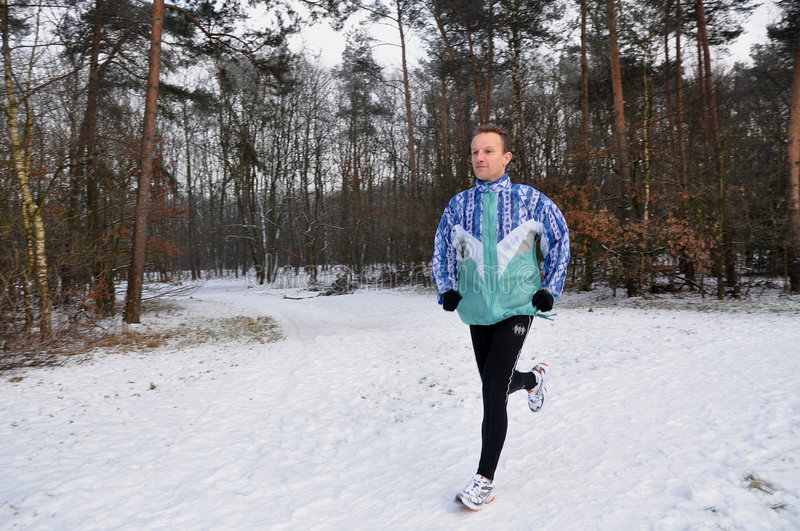 Young men running in winter stock photography